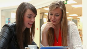 Happy friends having coffee together using tablet. In a cafe stock footage