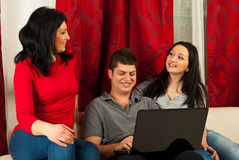 Happy friends having conversation on sofa. Happy three friends having conversation and using laptop in living room Royalty Free Stock Images