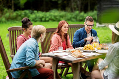 Happy friends having dinner at summer garden party Stock Image