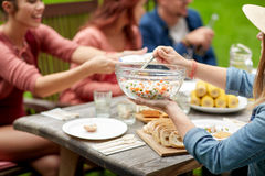 Happy friends having dinner at summer garden party Royalty Free Stock Images