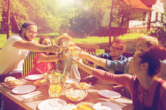 Happy friends having dinner at summer garden party. Leisure, holidays, eating, people and food concept - happy friends having dinner at summer garden party Royalty Free Stock Photography