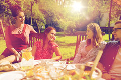 Happy friends having dinner at summer garden party Royalty Free Stock Photography