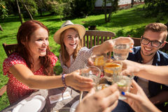 Happy friends having dinner at summer garden party Royalty Free Stock Image