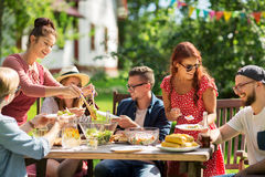 Happy friends having dinner at summer garden party. Leisure, holidays, eating, people and food concept - happy friends having dinner and sharing salad at summer Stock Image