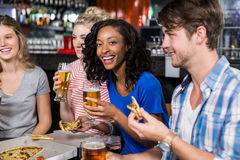 Happy friends having a drink and pizza Stock Image