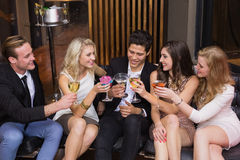 Happy friends having a drink together Stock Photos