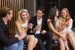 Happy friends having a drink together Royalty Free Stock Images