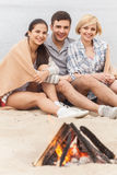 Happy friends having fun around bonfire. Royalty Free Stock Photos