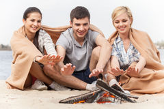 Happy friends having fun around bonfire. Royalty Free Stock Photography
