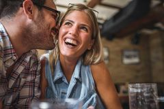 Happy friends having fun at bar - Young trendy couple drinking beer and laughing together. Happy friends group drinking beer at brewery bar restaurant stock images