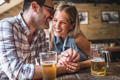 Happy friends having fun at bar - Young trendy couple drinking beer and laughing together. Happy friends group drinking beer at brewery bar restaurant stock image
