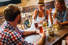 Happy friends having fun at bar - Young trendy people drinking beer and laughing together. Happy friends group drinking beer at brewery bar restaurant stock photography