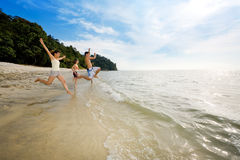 Happy friends having fun by the beach. Jumping into the sea Royalty Free Stock Photo
