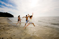 Happy friends having fun by the beach. Jumping into the sea Royalty Free Stock Image