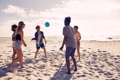 Happy friends having fun on the beach. Portrait of group of happy friends having fun on the beach and playing with ball on a summer day Royalty Free Stock Images