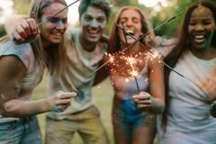 Friends burning fire sparkle sticks standing outdoors in a park royalty free stock image