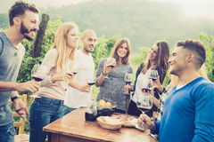 Happy friends having fun and drinink wine at backyard garden party. Happy friends having fun outdoor - Young people enjoying harvest time together at farmhouse Royalty Free Stock Images