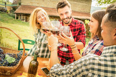 Happy friends having fun and drinking wine - Friendship concept. With young people enjoying harvest time together at farmhouse vineyard countryside Stock Images