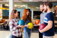 Cheerful friends bowling together Royalty Free Stock Image