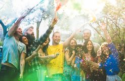 Happy friends having fun at garden party with multicolored smoke royalty free stock image
