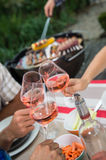 Happy friends having fun outdoors, hands toasting rose wine glass. Happy friends having fun outdoors, Focus on hands toasting rose wine glass during barbecue Stock Image
