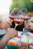 Happy friends having fun outdoors, hands toasting rose wine glass. Happy friends having fun outdoors, Focus on hands toasting rose wine glass during barbecue Royalty Free Stock Image