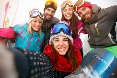 Happy friends having fun on snow. Snowbarders and skiers group t. Eam friendship making selfie Royalty Free Stock Photos
