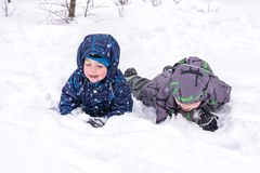Happy friends having fun with snow. Two funny little kid boys in colorful clothes playing outdoors. Active leisure with children in winter on cold snowy days Stock Image