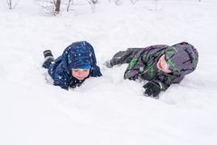 Happy friends having fun with snow. Two funny little kid boys in colorful clothes playing outdoors. Active leisure with children in winter on cold snowy days Royalty Free Stock Photo