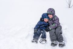 Happy friends having fun with snow. Two funny little kid boys in colorful clothes playing outdoors. Active leisure with children in winter on cold snowy days Royalty Free Stock Images