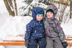 Happy friends having fun with snow. Two funny little kid boys in colorful clothes playing outdoors. Active leisure with children in winter on cold snowy days Stock Photos