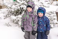Happy friends having fun with snow. Two funny little kid boys in colorful clothes playing outdoors. Active leisure with children in winter on cold snowy days Stock Images