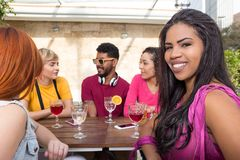 Happy friends having fun together at cafe bar outdoor. Summer, warm, friendship, diversity, reunion concept stock image