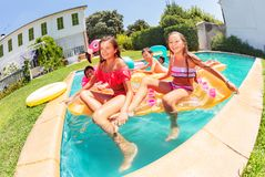 Happy friends having fun together in swimming pool royalty free stock images