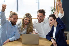 Happy friends having fun while using laptop. In caf Royalty Free Stock Images