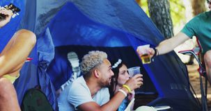 Friends having glass of beer in tent at music festival 4k. Happy friends having glass of beer in tent at music festival 4k stock video footage