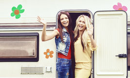 Happy friends are having a good time together in camper trailer. Stock Photography