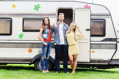 Happy friends are having a good time together in camper trailer. Royalty Free Stock Photos