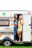 Happy friends are having a good time together in camper trailer. Stock Photos