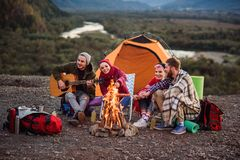 Happy friends having a picnic at the mountains, they are chatting, drinking energy drinks, playing on guitar and bake. Happy group of friends having a picnic at stock photo