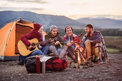 Happy friends having a picnic at the mountains, they are chatting, drinking energy drinks, playing on guitar and bake. Happy group of friends having a picnic at royalty free stock images