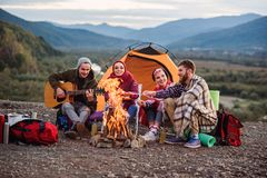 Happy friends having a picnic at the mountains, they are chatting, drinking energy drinks, playing on guitar and bake. Happy group of friends having a picnic at stock image