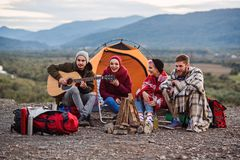 Happy friends having a picnic at the mountains, they are chatting, drinking energy drinks, playing on guitar and bake. Happy group of friends having a picnic at stock images