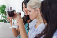 Happy friends having red wine together. At home on couch Royalty Free Stock Images