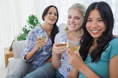 Happy friends having white wine together looking at camera. At home on couch Royalty Free Stock Image