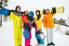 Happy friends in helmets with snowboards outdoors Royalty Free Stock Photos