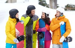Happy friends in helmets with snowboards talking Royalty Free Stock Images