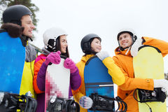 Happy friends in helmets with snowboards talking. Winter, leisure, extreme sport, friendship and people concept - happy friends in helmets with snowboards Stock Image