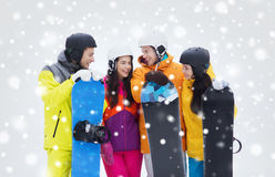 Happy friends in helmets with snowboards talking Stock Photography