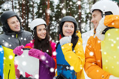 Happy friends in helmets with snowboards talking. Winter, leisure, extreme sport, friendship and people concept - happy friends in helmets with snowboards Stock Images